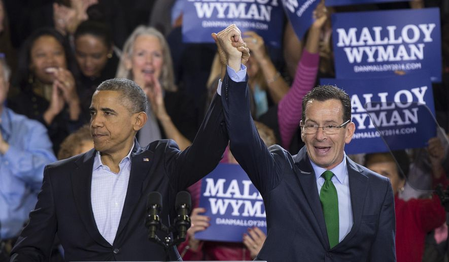 President Barack Obama raises the hand of Connecticut Gov. Dannel P. Malloy, right, during a rally at Central High School in Bridgeport, Conn. Sunday, Nov. 2, 2014. Obama visited Bridgeport to rally the heavily Democratic city in an effort to re-elect Malloy in Tuesday's midterm election where he will rematch with GOP candidate Tom Foley. (AP Photo/John Minchillo)