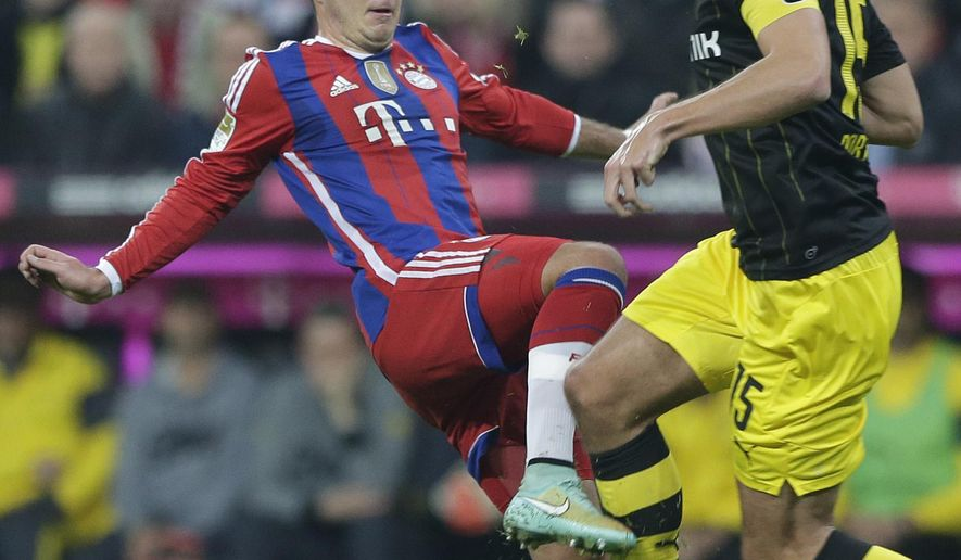 Bayern's Mario Goetze, left, and Dortmund's Mats Hummels challenge for the ball during the German first division Bundesliga soccer match between FC Bayern and Borussia Dortmund in the Allianz Arena in Munich, Germany, Saturday, Nov. 1, 2014. (AP Photo/Matthias Schrader)