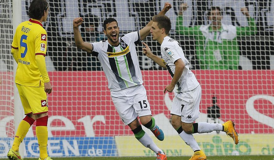 Moenchengladbach's Alvaro Dominguez from Spain, center, and Moenchengladbach's Patrick Herrmann celebrate after scoring during the German first division Bundesliga soccer match between Borussia Moenchengladbach and TSG Hoffenheim in Moenchengladbach, Germany, Sunday, Nov. 2, 2014. (AP Photo/Frank Augstein)