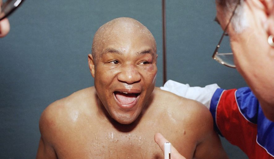 A jubilant George Foreman talks with one of his corner men in his locker room after knocking out Michael Moorer in the 10th round in Las Vegas on Saturday, Nov. 5, 1994. (AP Photo/Lennox McLendon)