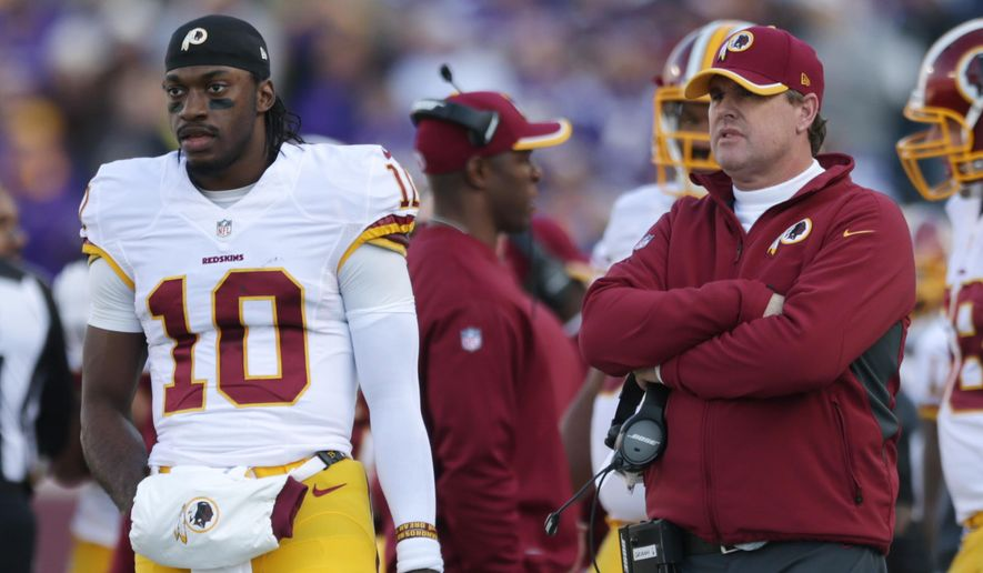 Washington Redskins quarterback Robert Griffin III, left, stands on the sidelines with head coach Jay Gruden, right, during the first half of an NFL football game against the Minnesota Vikings, Sunday, Nov. 2, 2014, in Minneapolis. The Vikings won 29-26. (AP Photo/Jim Mone)