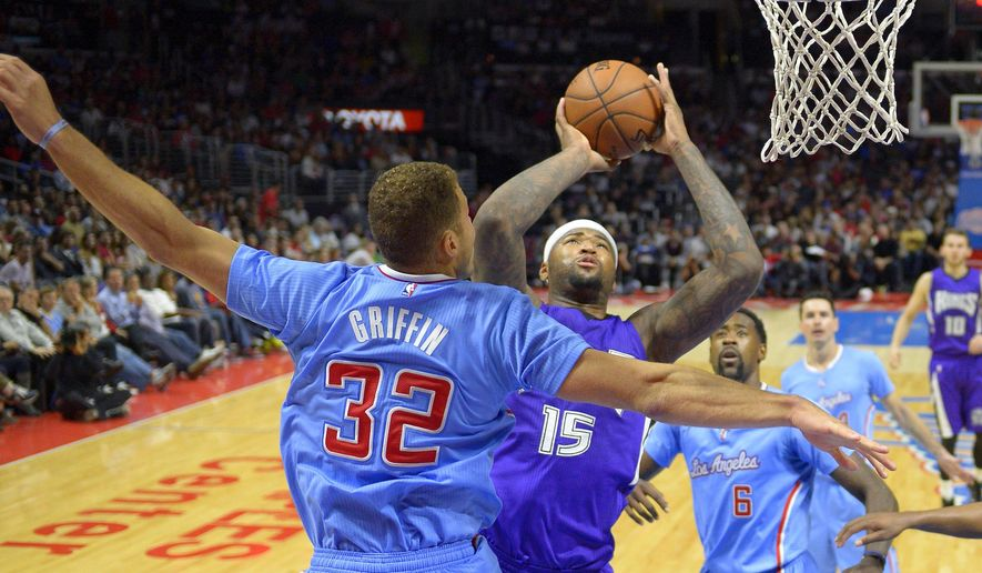 Sacramento Kings center DeMarcus Cousins, second from left, puts up a shot as Los Angeles Clippers forward Blake Griffin, left, defends during the first half of an NBA basketball game, Sunday, Nov. 2, 2014, in Los Angeles.  (AP Photo/Mark J. Terrill)