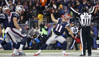New England Patriots wide receiver Julian Edelman (11) celebrates a touchdown catch from quarterback Tom Brady, far left, in the first half of an NFL football game against the Denver Broncos on Sunday, Nov. 2, 2014, in Foxborough, Mass. Patriots tight end Rob Gronkowski, second from left, watches. (AP Photo/Elise Amendola)