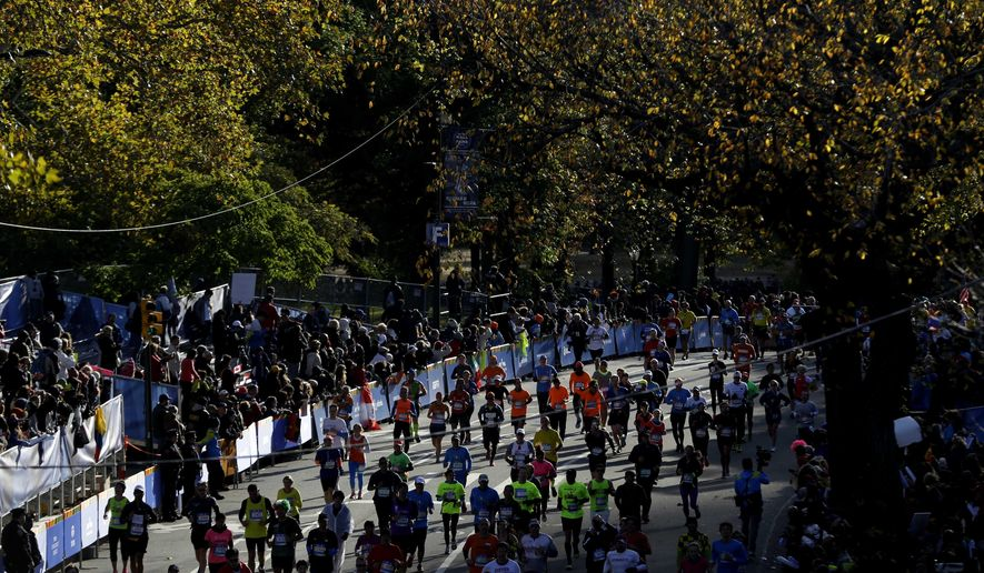 Runners approach the finish line of the 2014 New York City Marathon in New York, Sunday, Nov. 2, 2014. (AP Photo/Seth Wenig)