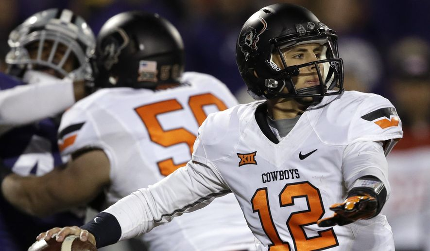 Oklahoma State quarterback Daxx Garman (12) passes to a teammate during the second half of an NCAA college football game against Kansas State in Manhattan, Kan., Saturday, Nov. 1, 2014. Kansas State defeated Oklahoma State 48-14. (AP Photo/Orlin Wagner)