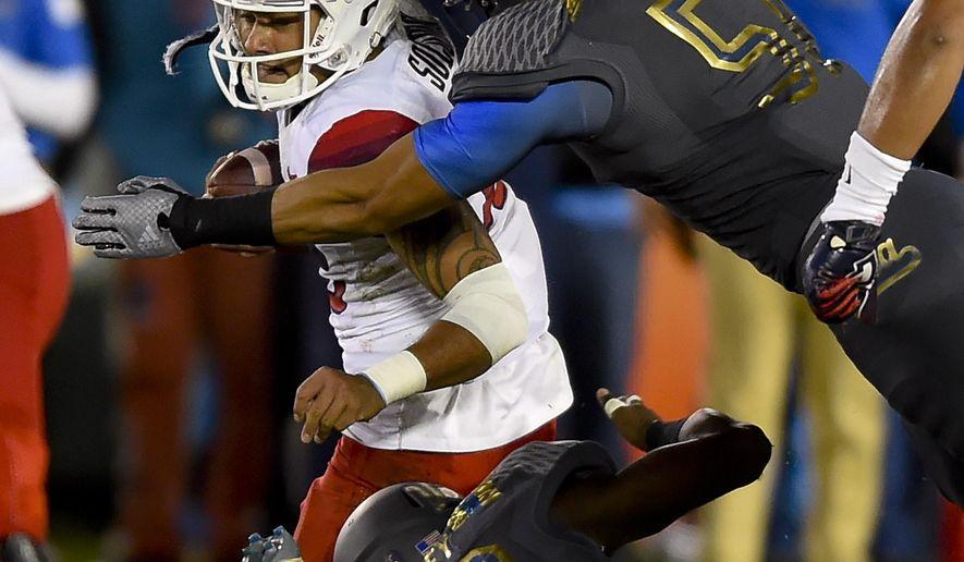 UCLA defensive lineman Takkarist McKinley (98) and linebacker Aaron Wallace (51) sack Arizona quarterback Anu Solomon during the second half of an NCAA college football game, Saturday, Nov. 1, 2014, in Pasadena, Calif. UCLA won 17-7. (AP Photo/Gus Ruelas)
