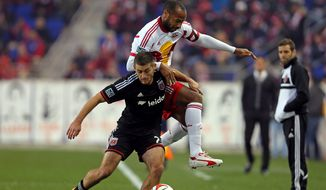 D.C. United defender Chris Korb battles for the ball with New York Red Bulls forward Thierry Henry during the first half of an MLS playoff soccer match, Sunday, Nov. 2, 2014, in Harrison, N.J. (AP Photo/Adam Hunger)