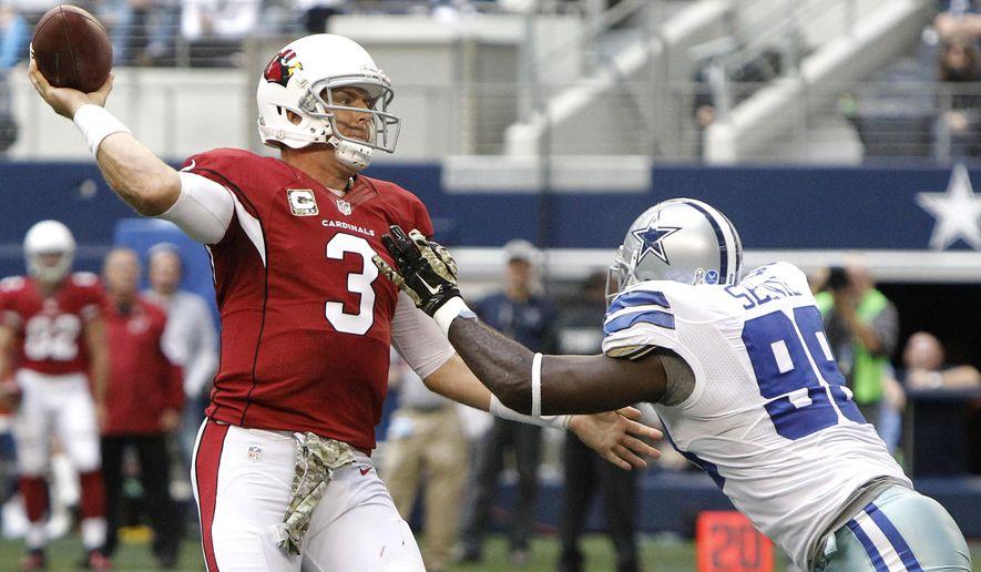 Arizona Cardinals quarterback Carson Palmer (3) passes as Dallas Cowboys defensive end George Selvie (99) defends during the second half of an NFL football game Sunday, Nov. 2, 2014, in Arlington, Texas. (AP Photo/Brandon Wade)