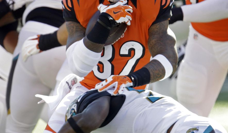 Cincinnati Bengals running back Jeremy Hill, top, is tackled by Jacksonville Jaguars linebacker Jeremiah George during the first half of an NFL football game in Cincinnati, Sunday, Nov. 2, 2014. (AP Photo/AJ Mast)