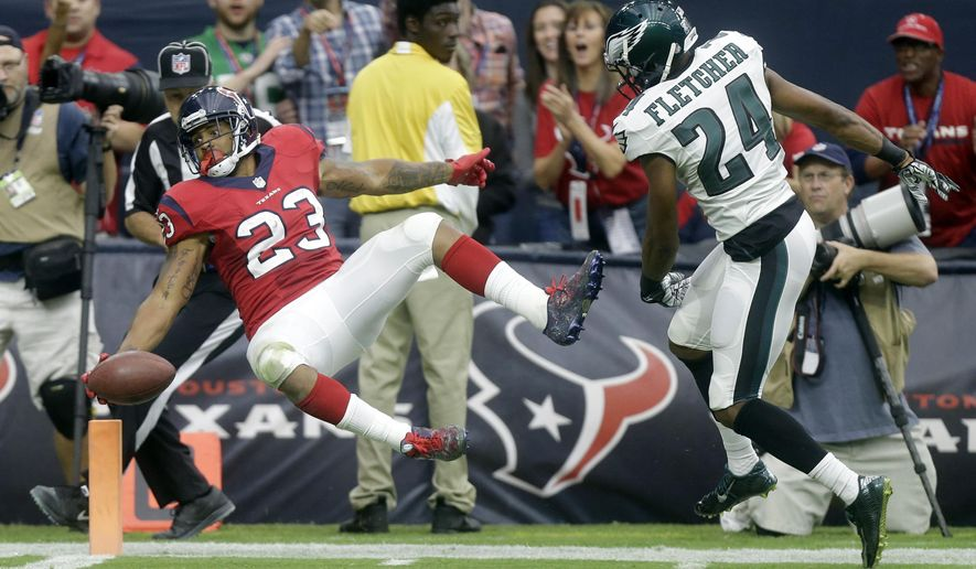 Houston Texans running back Arian Foster, left, falls into the end zone after catching a 56-yard pass for a touchdown as Philadelphia Eagles cornerback Bradley Fletcher, right, defends during the second quarter of an NFL football game, Sunday, Nov. 2, 2014, in Houston. (AP Photo/Patric Schneider)