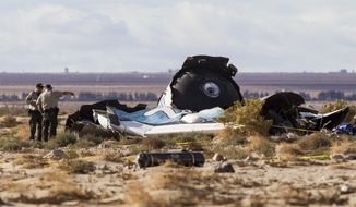 Law enforcement officers take a closer look at the wreckage near the site where a Virgin Galactic space tourism rocket, SpaceShipTwo, exploded and crashed in Mojave, Calif. Saturday, Nov 1, 2014. The explosion killed a pilot aboard and seriously injured another while scattering wreckage in Southern California's Mojave Desert, witnesses and officials said. (AP Photo/Ringo H.W. Chiu)