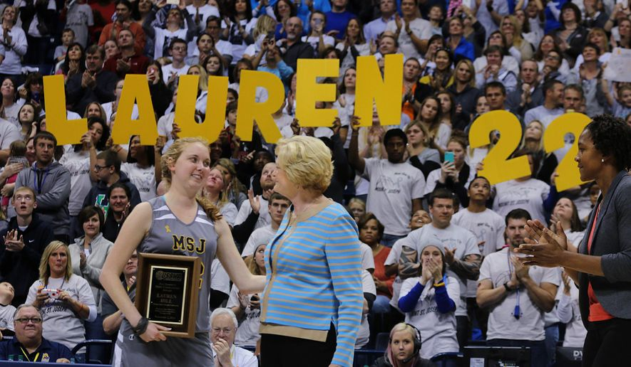 Mount St. Joseph's Lauren Hill hugs Pat Summit after receiving the Pat Summitt Award during halftime of her first NCAA college basketball game against Hiram University at Xavier University in Cincinnati on Sunday, Nov. 2, 2014. The NCAA allowed Mount St. Joseph's season opener to be moved up to Nov. 2, so that Hill, who has an inoperable brain tumor, to be able to play in a college basketball game. WNBA Player Tamika Devonne Catchings, of the Indiana Fever is at the right. (AP Photo/Tom Uhlman)