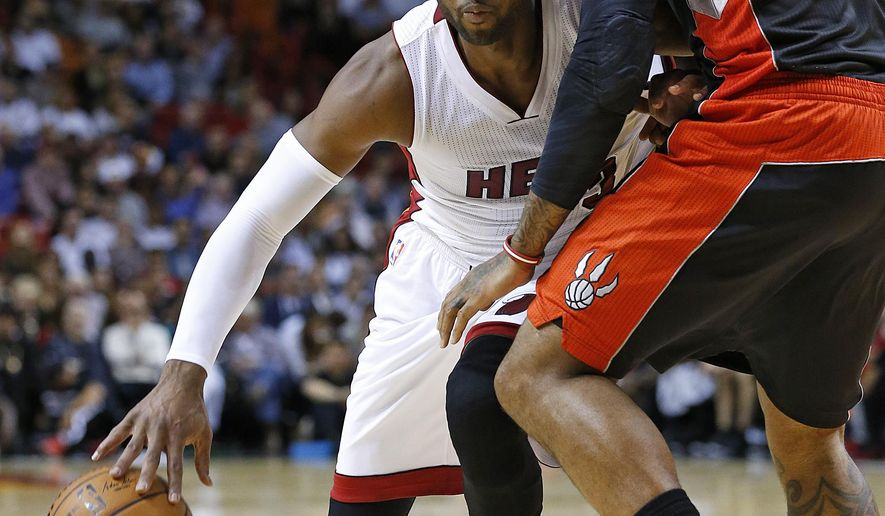 Miami Heat's Dwyane Wade (3) dribbles to the basket against Toronto Raptors' James Johnson (3) during the first half of an NBA basketball game in Miami, Sunday, Nov. 2, 2014. (AP Photo/Joel Auerbach)