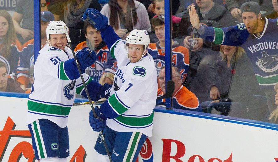 Vancouver Canucks' Linden Vey (7) celebrates his goal on the Edmonton Oilers with teammate Dorsett Derek (51) during the second period of an NHL hockey game Saturday, Nov. 1, 2014, in Edmonton, Alberta. (AP Photo/The Canadian Press, Amber Bracken)