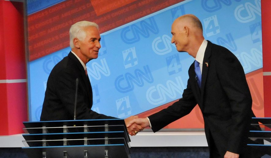 In this Oct. 21, 2014, file-pool photo, Florida Democratic gubernatorial candidate Charlie Crist, left, shakes hands with Gov. Rick Scott their debate in Jacksonville, Fla. (AP Photo/The Florida Times-Union, Will Dickey, File-Pool)