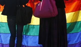 Members of the Montenegrin gay community hold a rainbow flag during a gay pride march in Podgorica, Montenegro, Sunday, Nov. 2, 2014. Protected by hundreds of riot police, about two hundred gay activists marched peacefully in Montenegro, a staunchly conservative Balkan country seeking EU membership.(AP Photo/Darko Vojinovic) ** FILE **