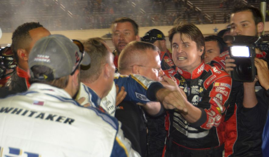 Pit crew members for drivers Jeff Gordon and Brad Keselowski fight on pit row after the end of the NASCAR Sprint Cup Series auto race at Texas Motor Speedway in Fort Worth, Texas, Sunday, Nov. 2, 2014.  Keselowski made contact with Gordon's on a restart that knocked Gordon out of of the race.  (AP Photo/Randy Holt)