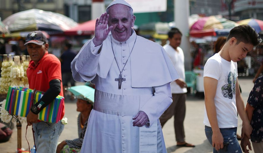Filipinos pass by a cutout of Pope Francis during a gathering of relatives of missing left-wing activists in Manila, Philippines as they observe All Souls Day on Sunday, Nov. 2, 2014. The group said they are asking Pope Francis to intercede in seeking justice for their missing loved ones. Having no grave or cemetery to visit, the relatives gather each year, bearing candles and flowers, and demand that the government take steps to produce their loved ones, dead or alive. (AP Photo/Aaron Favila)