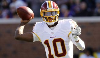 Washington Redskins quarterback Robert Griffin III throws a pass during the first half of an NFL football game against the Minnesota Vikings, Sunday, Nov. 2, 2014, in Minneapolis. (AP Photo/Ann Heisenfelt)