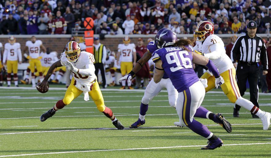 Washington Redskins quarterback Robert Griffin III, left, scrambles under pressure during the second half of an NFL football game against the Minnesota Vikings, Sunday, Nov. 2, 2014, in Minneapolis. (AP Photo/Ann Heisenfelt)