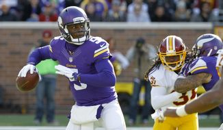 Minnesota Vikings quarterback Teddy Bridgewater, left, drops back for a pass under pressure from Washington Redskins during the first half of an NFL football game, Sunday, Nov. 2, 2014, in Minneapolis. (AP Photo/Ann Heisenfelt)