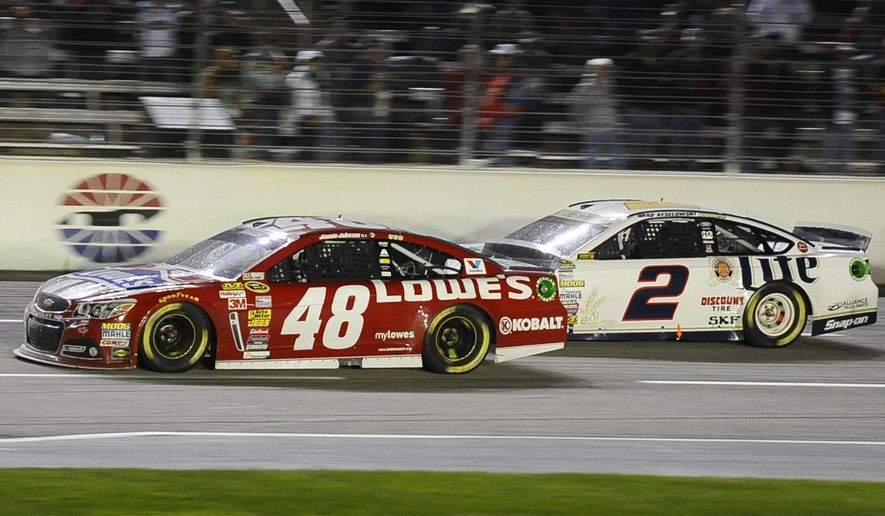 Jimmie Johnson (48) pulls ahead of Brad Keselowski (2) on the final restart of the NASCAR Sprint Cup Series auto race at Texas Motor Speedway in Fort Worth, Texas, Sunday, Nov. 2, 2014. (AP Photo/Ralph Lauer)
