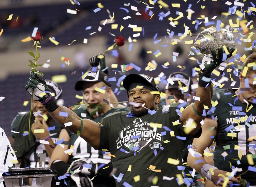 FILE - This Dec. 8, 2013, file photo,  shows Michigan State's Denicos Allen holding up the trophy following the Big Ten Conference championship NCAA college football game against Ohio State in Indianapolis. Just as No. 13 Ohio State has been waiting for 11 months for another shot at Michigan State, watchers of the Buckeyes have been waiting to see what they might do against a team with comparable talent. After six straight games beating up on lesser opponents, now the Buckeyes, and their doubters, will see just how good they are. (AP Photo/AJ Mast, File)