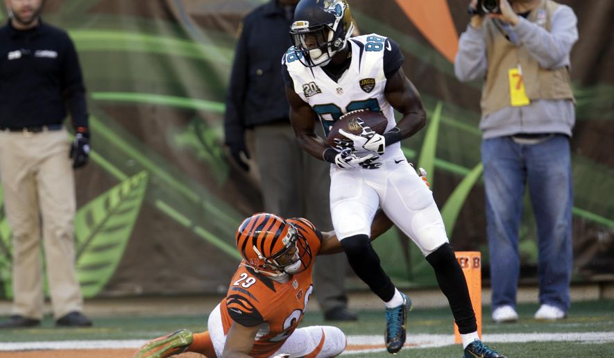 Jacksonville Jaguars wide receiver Allen Hurns, right, breaks the tackle of Cincinnati Bengals cornerback Leon Hall to score a touchdown during the second half of an NFL football game in Cincinnati, Sunday, Nov. 2, 2014. (AP Photo/AJ Mast)