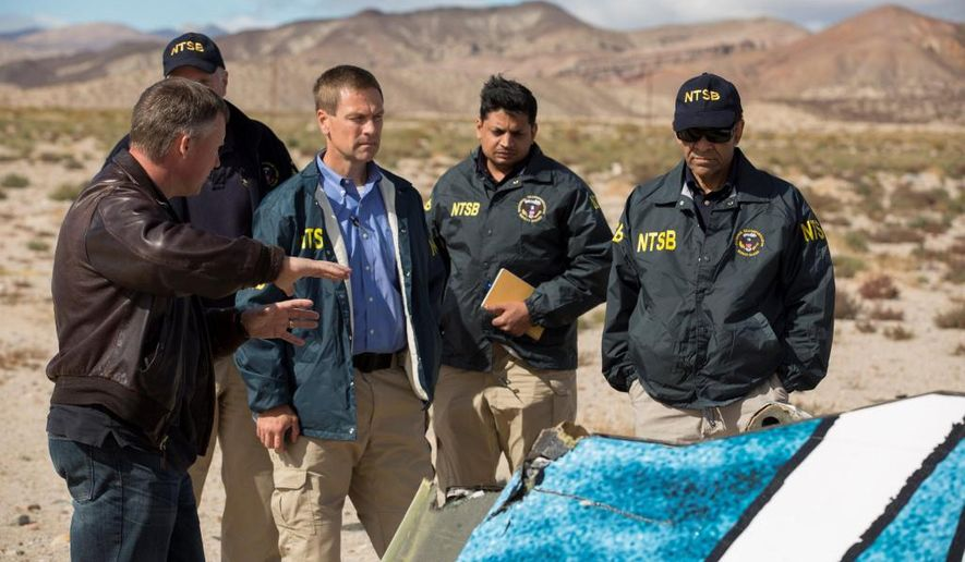 """In this Nov. 1, 2014, photo provided by the National Transportation Safety Board, Virgin Galactic pilot Todd Ericson, left, talks with NTSB Acting Chairman Christopher A. Hart, right, at SpaceShipTwo accident site with investigators in Mojave, Calif. The cause of Friday's crash of Virgin Galactic's SpaceShipTwo has not been determined, but investigators found the """"feathering"""" system, which rotates the tail to create drag, was activated before the craft reached the appropriate speed, National Transportation Safety Board Acting Chairman Christopher Hart said. (AP Photo/NTSB)"""