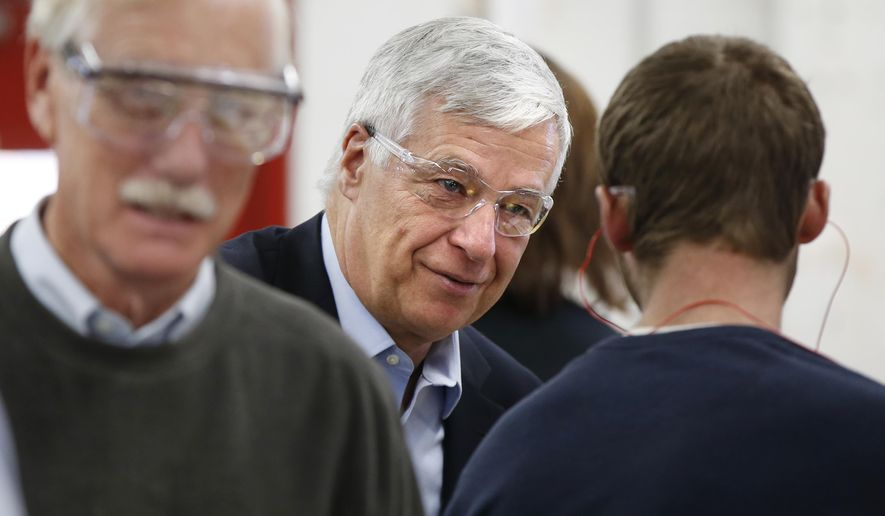 Democratic gubernatorial candidate Mike Michaud, center, campaigns with independent Sen. Angus King, left, at the New Balance shoe factory, Monday, Nov. 2, 2014, in Skowhegan, Maine. King initially endorsed independent gubernatorial candidate Elliot Cutler but switched his endorsement to Michaud last week. (AP Photo/Robert F. Bukaty)