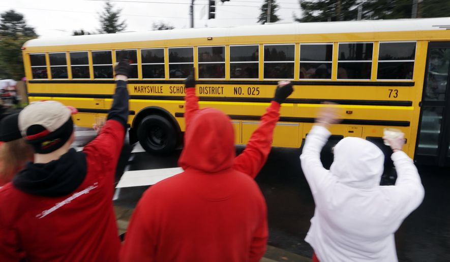 People dressed in the school colors of red and white cheer and wave as one of the first school buses carrying students on their return to Marysville-Pilchuck High School drives past Monday, Nov. 3, 2014, in Marysville, Wash. After the shock from the Oct. 24 shooting there that left four students dead, including the shooter, and two students still in a Seattle hospital, administrators and teachers hope to transition to a new routine. The day was scheduled to begin with a morning assembly. Lunch is in the gym because the cafeteria where the shooting took place remains closed. (AP Photo/Elaine Thompson)