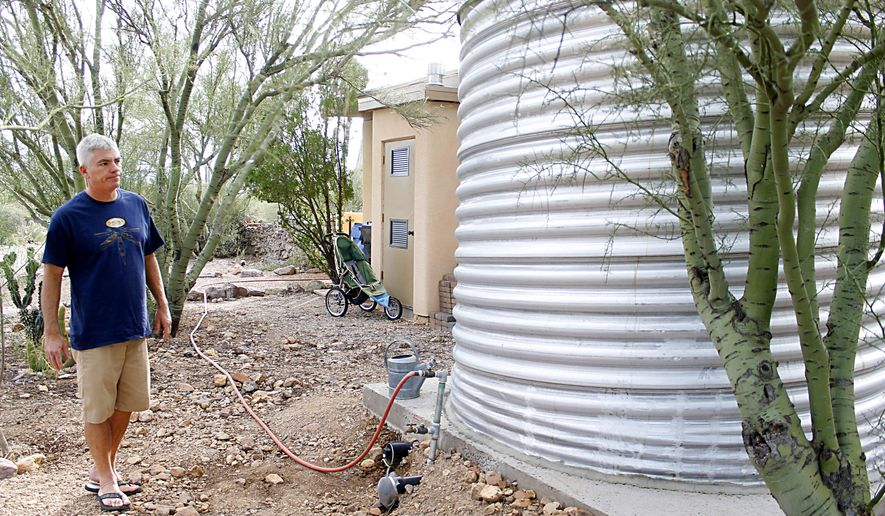 Scott Mencke looks over one of the three cisterns he built in his backyard for rainwater harvesting Saturday, Nov. 1, 2014, in Tucson, Ariz.  The main cistern holds 3,000 gallons of water, while the other two cisterns are connected to the other side of his home to catch rain water off of the other roofs.  Mencke received a rain harvesting rebate from Tucson Water for $2,000 and has been harvesting rainwater for a little over a year now. (AP Photo/Arizona Daily Star, Briana Sanchez)