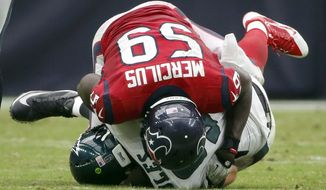 Philadelphia Eagles quarterback Nick Foles, bottom, is sacked for a 9-yard loss by Houston Texans linebacker Whitney Mercilus during the first quarter of an NFL football game, Sunday, Nov. 2, 2014, in Houston. Foles was injured on the play. (AP Photo/Tony Gutierrez)