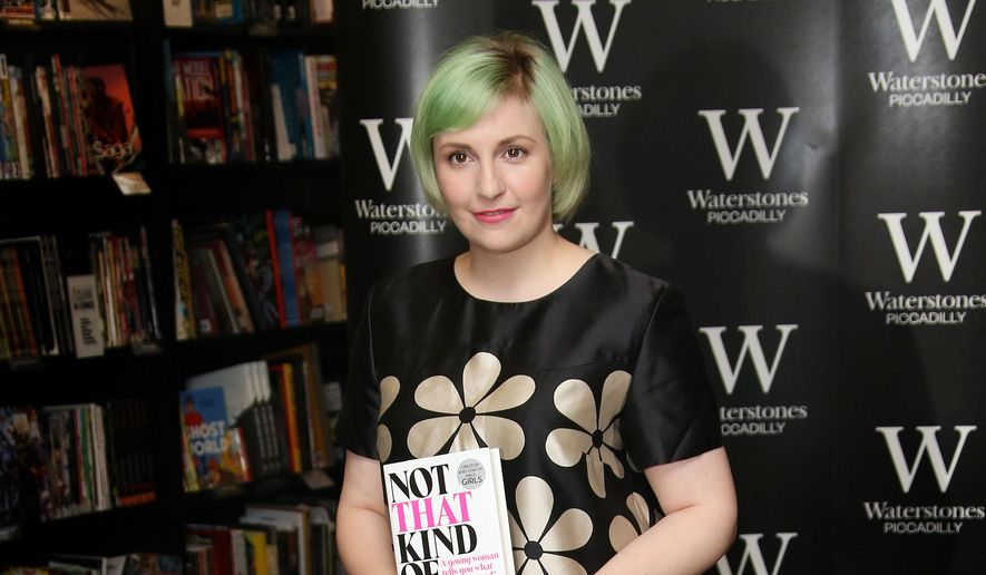 """In this Oct. 29, 2014, file photo, U.S. actress Lena Dunham holds her memoir, """"Not That Kind Of Girl,"""" ahead of a book signing at Waterstones book shop, Piccadilly in central London. (Photo by Joel Ryan/Invision/AP, File)"""