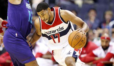 Washington Wizards guard Garrett Temple (17) drives against Charlotte Hornets guard Gary Neal (12) in the first half of a pre-season NBA basketball game, Friday, Oct. 17, 2014 in Washington. (AP Photo/Alex Brandon)