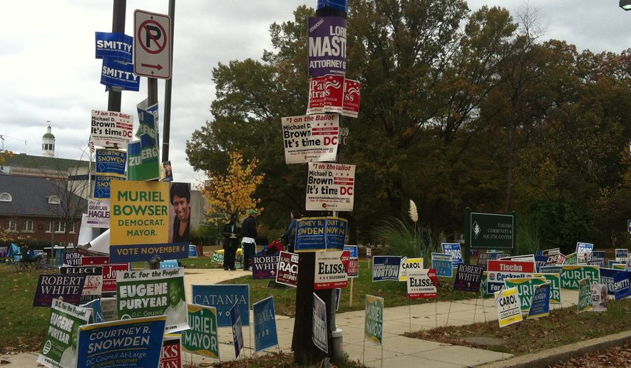 Campaign signs representing races across the city were posted outside an early voting site at the Takoma Community and Aquatic Center in Northwest D.C. on Saturday, the last day of voting ahead of Tuesday's elections. (Andrea Noble/The Washington Times)
