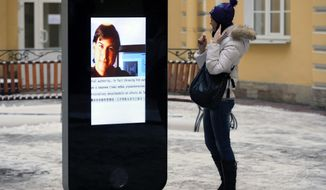 In this file photo dated Thursday, Jan. 10, 2013, a woman stands next to a screen showing a portrait of Steve Jobs on the recently erected memorial to late Apple Corp. co-founder in the courtyard of the Techno Park of the St. Petersburg National Research University of Information Technologies, Mechanics and Optics (ITMO University) in St. Petersburg, Russia.  The six-foot tall interactive iPhone shaped memorial has been taken down in response to last week's announcement that CEO of Apple, Tim Cook is openly gay. (AP Photo/Dmitry Lovetsky, FILE ) ** FILE **