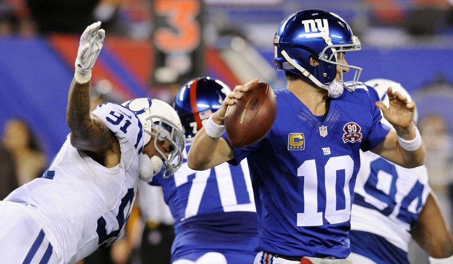 New York Giants quarterback Eli Manning (10) attempts to throw a pass as Indianapolis Colts' Jonathan Newsome (91) closes in during the second half of an NFL football game Monday, Nov. 3, 2014, in East Rutherford, N.J. Manning fumbles the ball and the Colts score a touchdown on the play. (AP Photo/Bill Kostroun)