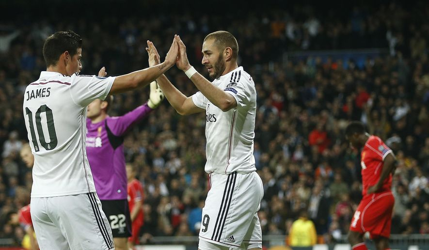 Real Madrid's Karim Benzema, centre, celebrates with James Rodriguez after scoring the opening goal during a Group B Champions League soccer match between Real Madrid and Liverpool at the Santiago Bernabeu stadium in Madrid, Spain, Tuesday Nov. 4, 2014. (AP Photo/Andres Kudacki)