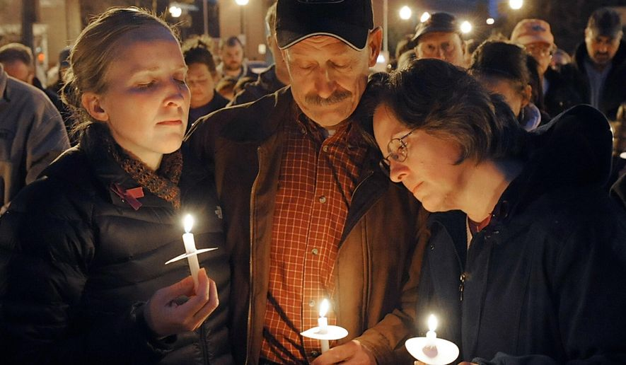 Jennifer Bruck, left, prays for her sister Chelsea Bruck with parents Matt and Leannda Bruck and other family with friends who turned to public prayer in Monroe, Mich., Monday, Nov. 3, 2014, as the police continue to search for the missing 22-year-old Maybee, Mich., woman. Dozens gathered in Loranger Square in Monroe to pray for the safe return of Chelsea who has been missing more than week. (AP Photo/Monroe News, Tom Hawley)
