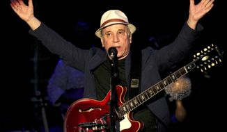 FILE - In a March 22, 2013 file photo, American songwriter and producer Paul Simon performs during the Timbre Rock and Roots concert in Singapore. Simon & Schuster, announced Tuesday, Nov. 4, 2014, that Simon has agreed to cooperate with author and longtime music critic Robert Hilburn for a planned biography. The publisher told The Associated Press that the book was currently untitled and did not yet have a release date.(AP Photo/Wong Maye-E, File)