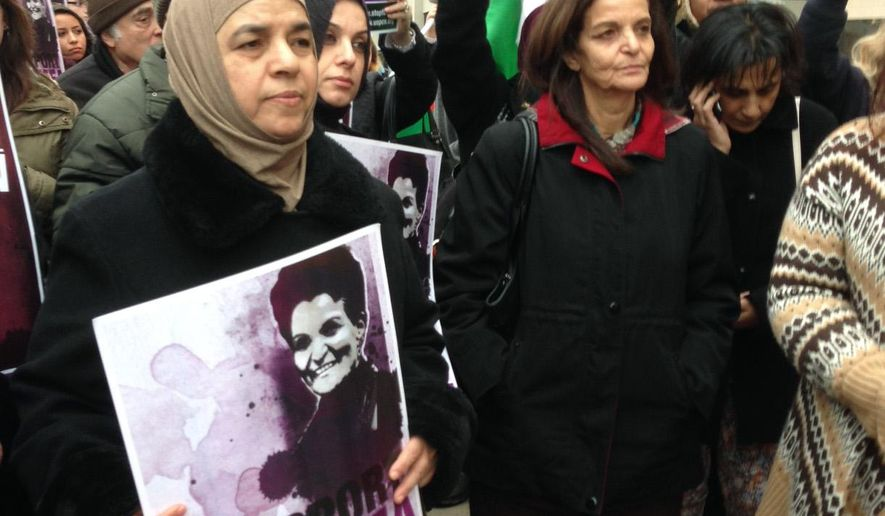 Rasmieh Odeh, center with red collar, stands among supporters outside federal court in Detroit on the opening day of her trial on Tuesday, Nov. 4, 2014. . Odeh, associate director at Chicago's Arab American Action Network, is charged with failing to tell U.S. immigration about her conviction for bombings in Israel in 1969 that killed two people at a supermarket. (AP Photo/Ed White)