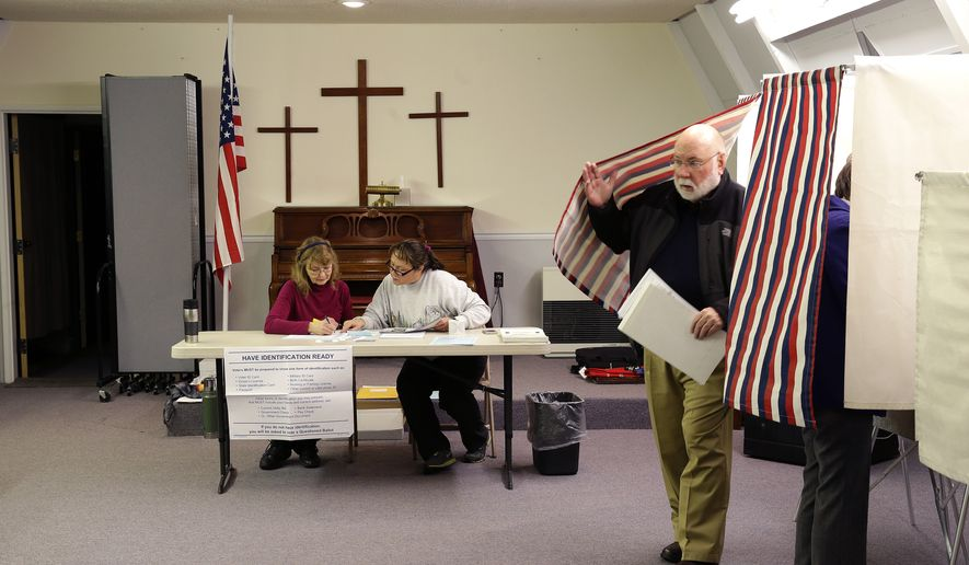 A voter leaves his booth as election workers GayLee Erickson, left, and Debbie Redmond, second from left, confer at the Valley Bible Chalet, on election day, Tuesday Nov. 4, 2014, in Indian, Alaska, south of Anchorage.  First-term Democratic Sen. Mark Begich is facing a strong challenge from Republican former state Attorney General Dan Sullivan.  (AP Photo/Ted S. Warren)