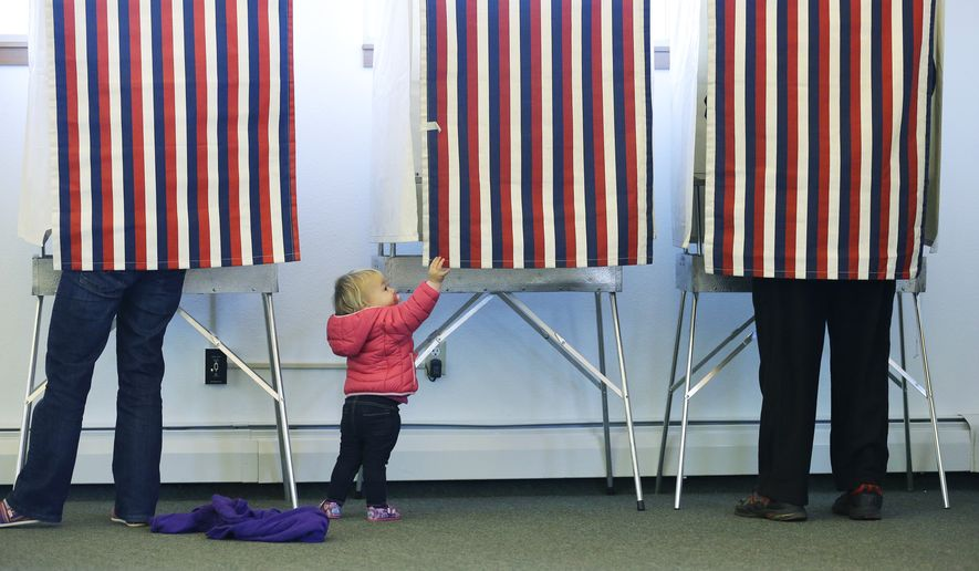 Zoe Buck, a 14-month-old child, checks out an empty voting booth as at her mother, Julie Buck, votes at left, Tuesday Nov. 4, 2014, at the Alaska Zoo polling place in Anchorage, Alaska. (AP Photo/Ted S. Warren)