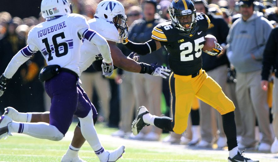 Iowa running back Akrum Wadley (25) stiff arms Northwestern linebacker Chi Chi Ariguzo (44) as Northwestern safety Godwin Igwebuike (16) comes to help with the tackle during the second half of an NCAA college football game, Saturday, Nov. 1, 2014, in Iowa City, Iowa . (AP Photo/Justin Hayworth)