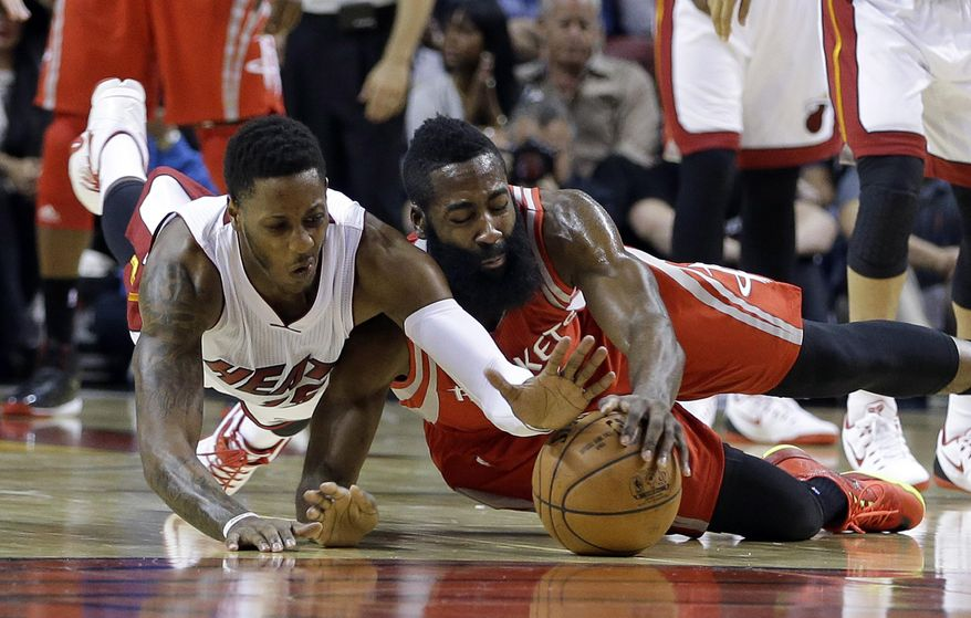 Miami Heat guard Mario Chalmers, left, battles Houston Rockets guard James Harden (13) for control of a loose ball in the first half of an NBA basketball game, in Miami,Tuesday, Nov. 4, 2014. (AP Photo/Alan Diaz)