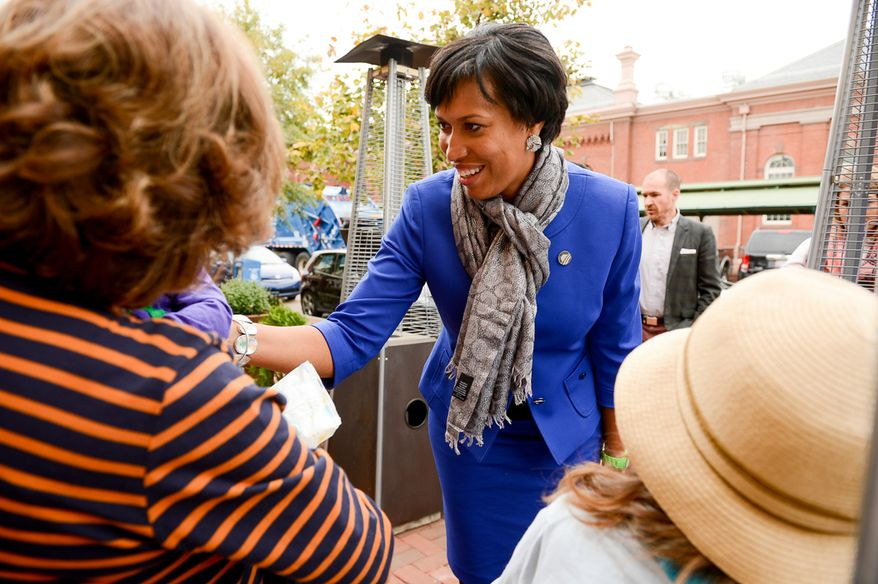 Democratic candidate for Mayor Muriel Bowser greets people on the street at Eastern Market on election day, Washington, D.C., Tuesday, November 4, 2014. (Andrew Harnik/The Washington Times)
