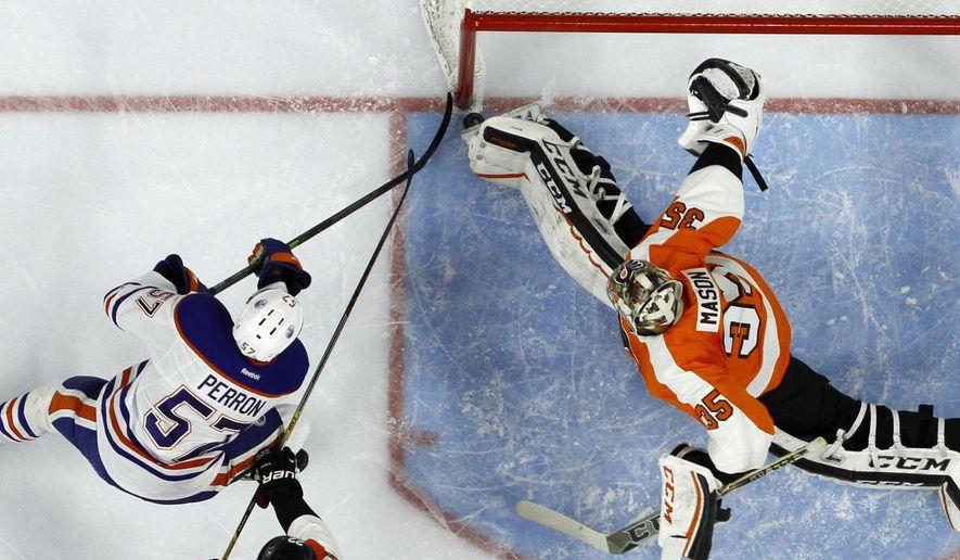 Philadelphia Flyers' Steve Mason, right, blocks a shot by Edmonton Oilers' David Perron during the third period of an NHL hockey game, Tuesday, Nov. 4, 2014, in Philadelphia. Philadelphia won 4-1. (AP Photo/Matt Slocum)