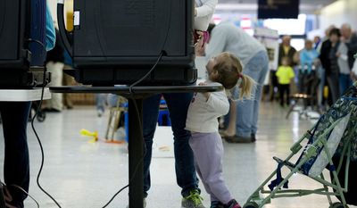 With her son, Reuben, 1, on her hip and daughter, Rebekah, 2, at her feet, Nicole Hutchinson, of Evansville, Ind., votes at Washington Square Mall Tuesday morning, Nov. 4, 2014. (AP Photo/The Evansville Courier & Press, Denny Simmons)