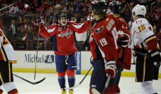 Washington Capitals left wing Alex Ovechkin, left, of Russia, celebrates a goal by teammate  Nicklas Backstrom (19), of Sweden, during the first period of an NHL hockey game as Calgary Flames Ladislav Smid (15) looks on, Tuesday, Nov. 4, 2014, in Washington. Ovechkin had an assist on the goal which made him the Capitals all-time franchise points leader. (AP Photo/Nick Wass)